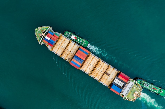 Shipping cargo container transportation on the green sea aerial view