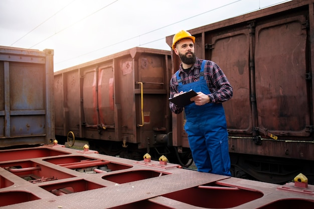 Shipping railroad worker with clipboard keeping track of cargo containers ready to leave the train station