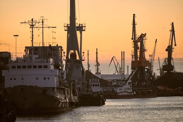 Корабли в морском порту на фоне заката. декорации индустриального пейзажа с контейнерными кранами и судами.