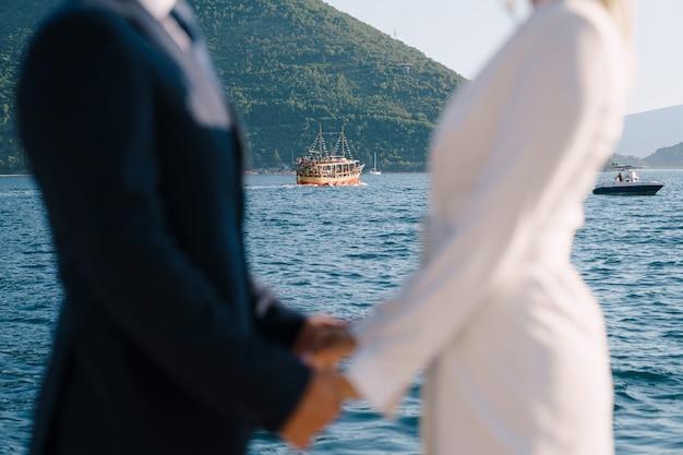 신혼 부부가 배경에서 손을 잡고 바다에서 항해하는 배