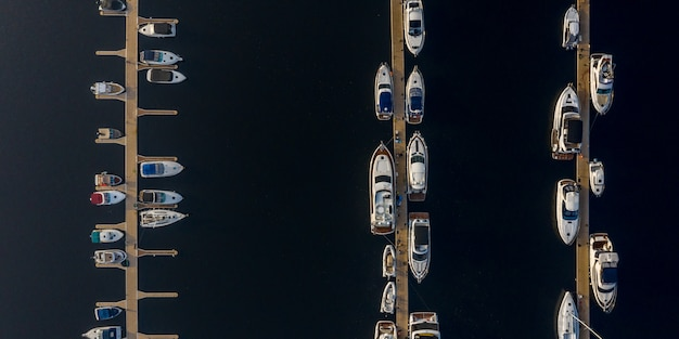 Ships, yachts, sailboats and boats moored at the river pier.