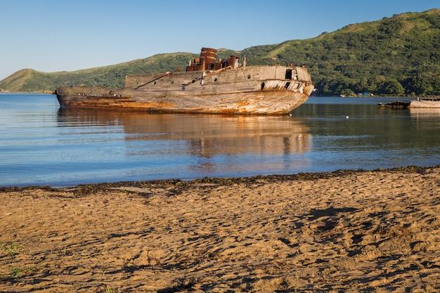 Shipwreck near the beach in calm bay in russia