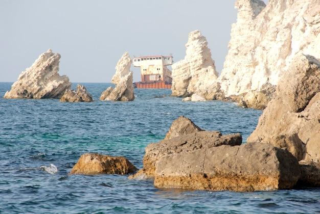 難破船。山の海岸近くのさびた貨物船