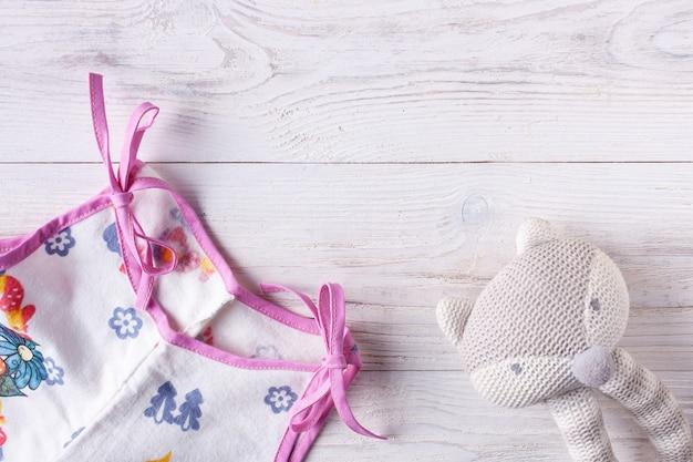 Рубашка для новорожденного и погремушка на светлом деревянном фоне