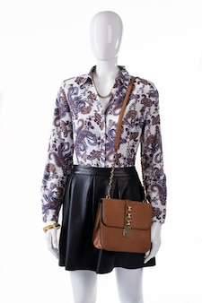 Shirt and handbag on mannequin. woman's floral shirt and accessories. girl's evening apparel with purse. precious jewelry and stylish look.