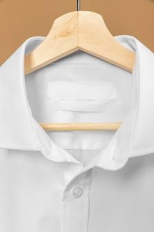 Camicia sul gancio con il primo piano dell'etichetta dello spazio della copia di informazioni
