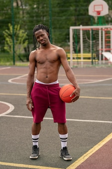 훈련 후 농구 코트 또는 경기장에 서있는 공을 가진 벗은 아프리카 근육질의 남자