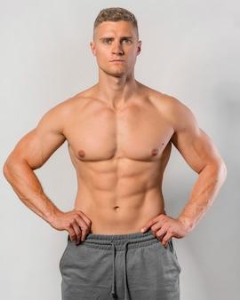 Без рубашки и подтянутый мужчина позирует, чтобы похвастаться телом