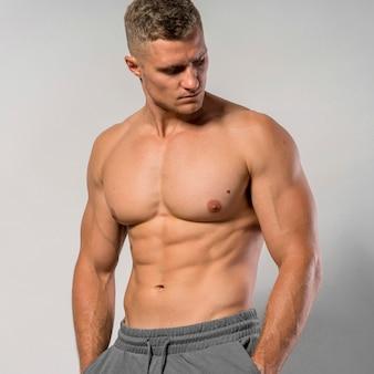 Без рубашки и подтянутый мужчина позирует