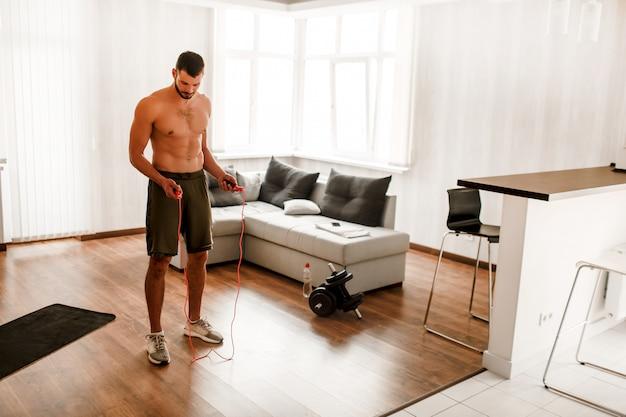 上半身裸のアスリートが自宅で縄跳びでトレーニングをしています