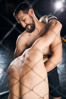 Shirtless athlete holding the opponent head in his arms during a sparring fight