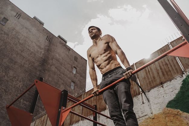 Спортсмен без рубашки занимается художественной гимнастикой с умными часами на запястье.
