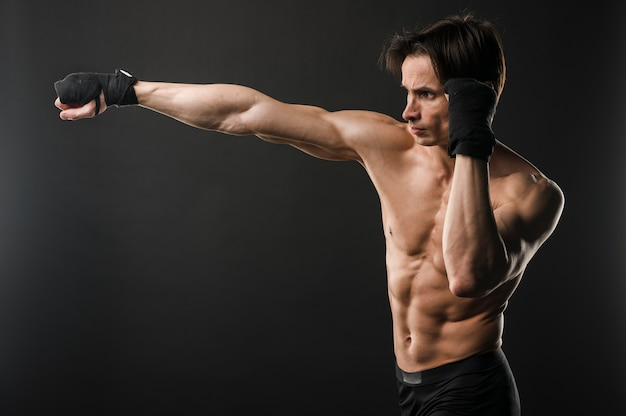 Shirtless athletic man boxing with copy space