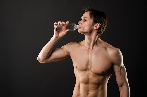 Shirtless athletic man drinking from water bottle