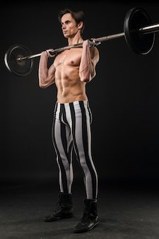 Shirtless athletic man lifting weights