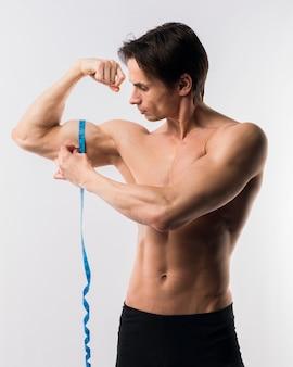Shirtless athletic man measuring biceps
