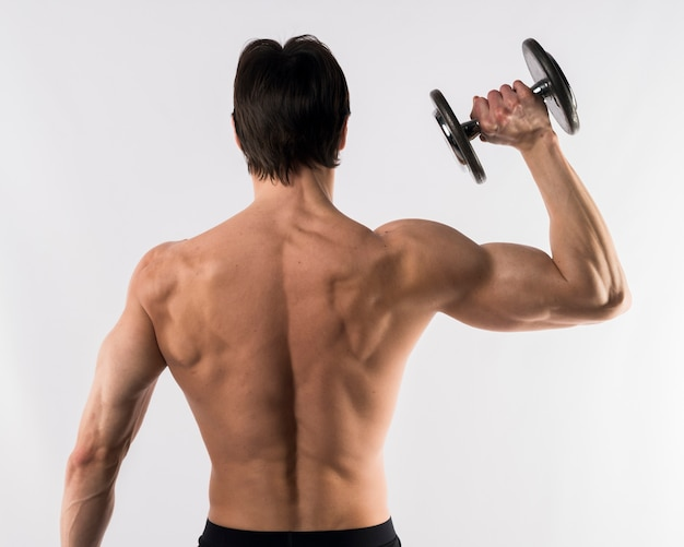 Shirtless athletic man showing off back muscles while holding weight