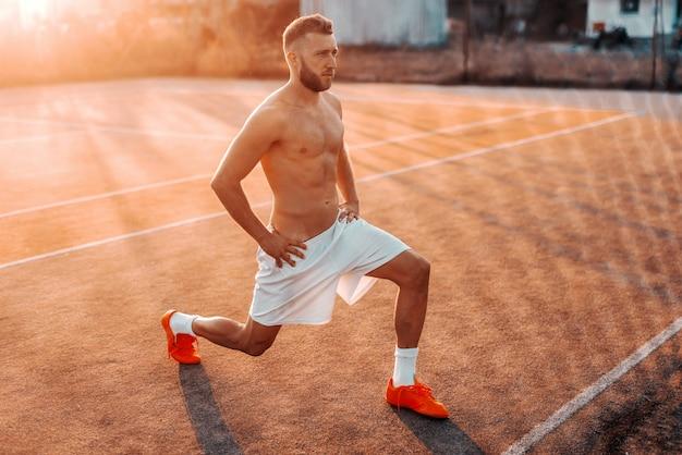 Без рубашки бородатый мужчина кавказской в шортах, вытянув ноги перед тренировкой на площадке утром в летнее время.