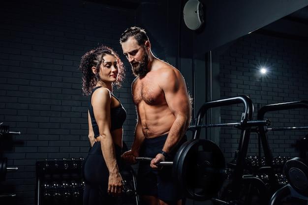 어두운 체육관에서 매력적인 아가씨 근처에 서있는 동안 무거운 바벨로 운동을하는 벗은 수염 난 남자