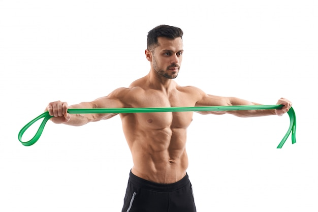 Shirtless bodybuilder holding resistance band.