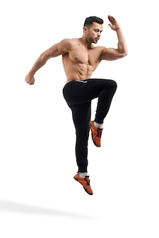 Shirtless bodybuilder jumping in place.