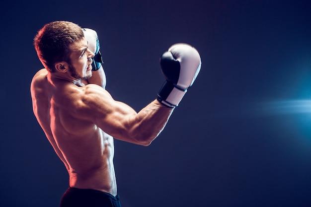Боксер без рубашки с перчатками на темном фоне. изолировать