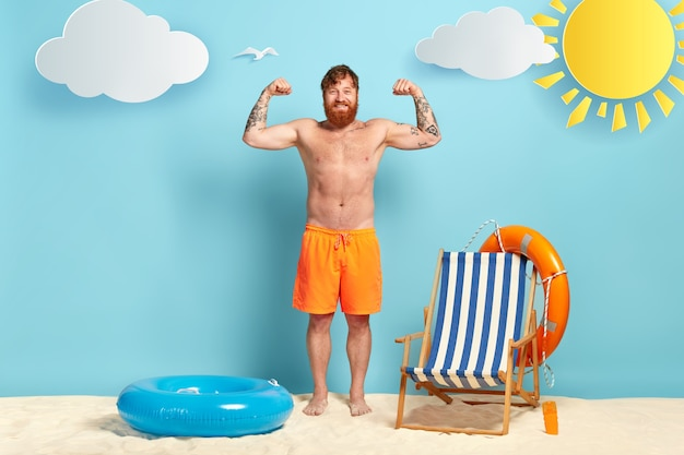 Shirtless 쾌활한 생강 남자가 팔을 들고, 근육을 보여주고, 문신을하고, 주황색 반바지를 입고, 모래 위에 포즈를 취합니다.