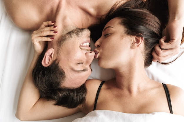 Shirtless couple 30s hugging together, while lying in bed at home or hotel apartment