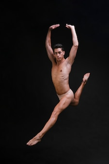 Shirtless dancer jumping with raised arms