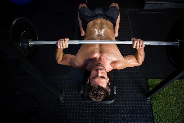Определенный человек без рубашки, тренирующийся со штангой