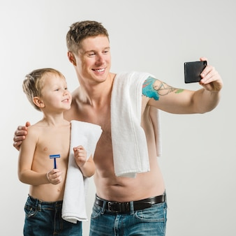 Shirtless father and son with white towels over their shoulders taking selfie on smartphone against white backdrop