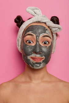 La donna asiatica felice a torso nudo applica una maschera di bellezza nera, gode di procedure anti wrikle o anti gonfiore, trattamenti termali, ha due panini pettinati, indossa la fascia, isolato su un muro roseo