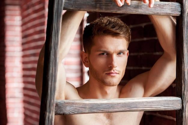 上半身裸のハンサム。木製のはしごに寄りかかって、レンガの壁の近くに立っている間カメラを見ているハンサムな若い上半身裸の男のクローズアップ