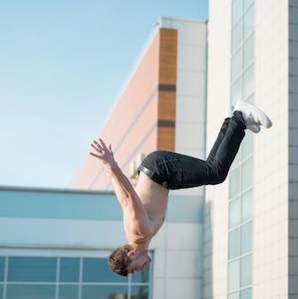 Shirtless hip hop performer posing mid-air