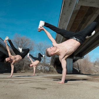 Shirtless hip hop performers practicing dance routine