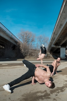 Shirtless hip hop performers practicing outside