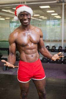 Shirtless macho man in santa hat at the gym
