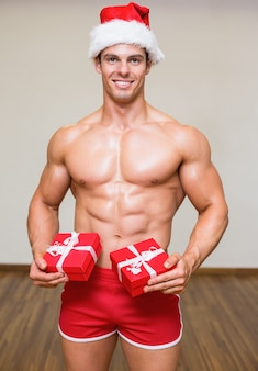 Shirtless macho man in santa hat holding gifts