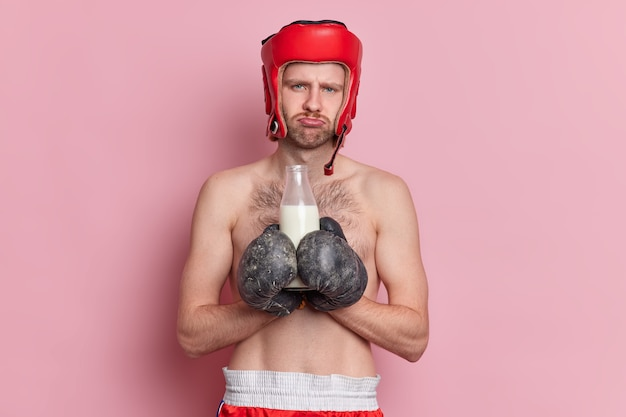 Shirtless male boxer has displeased face expression holds bottle of milk wears sport gloves feels tired after training.