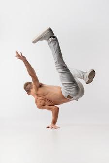 Танцор без рубашки в джинсах и кроссовках позирует во время танца