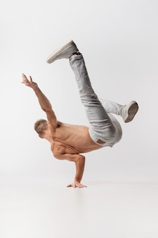 Shirtless male dancer in jeans and sneakers posing while dancing