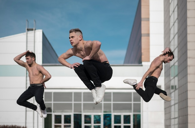 Shirtless male hip hop artists posing mid-air