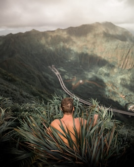 Shirtless male sitting in tall grass on a high hill with cliffs in the background
