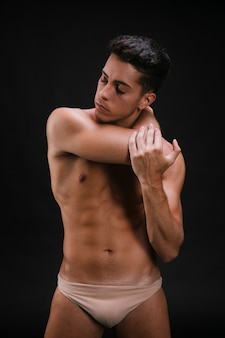 Shirtless male stretching neck and arm