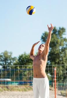 Giocatore di pallavolo maschio senza camicia sulla spiaggia che gioca con la palla