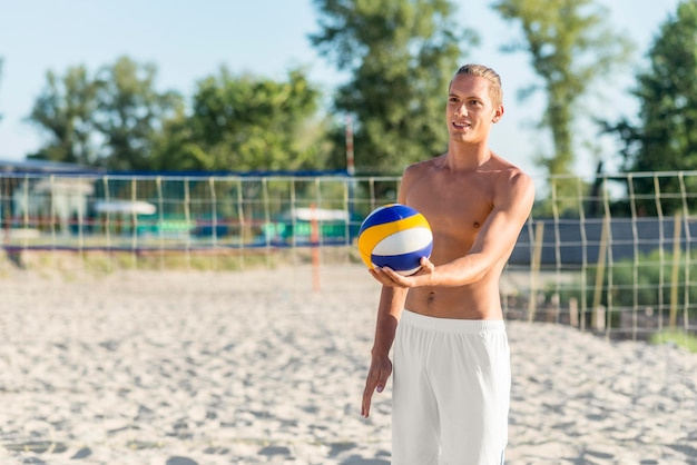 ボールを保持しているビーチで上半身裸の男性のバレーボール選手