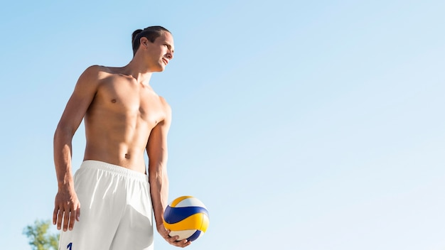 Shirtless male volleyball player preparing to serve ball with copy space