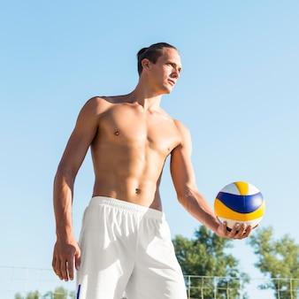 Giocatore di pallavolo maschio senza camicia che si prepara a servire la palla