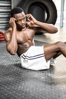 Shirtless man doing abdominal crunches at the crossfit gym