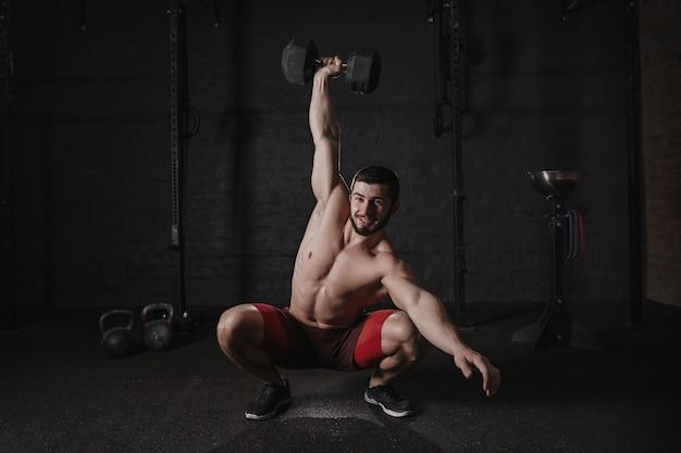 ダンベルスクワットをして笑っている上半身裸の男。ファンクショナルトレーニングをしているハンサムなクロスフィットアスリート。